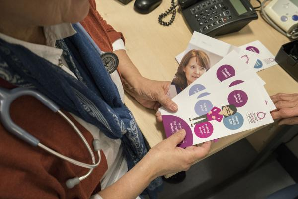 A GP holding ovarian cancer symptoms leaflets