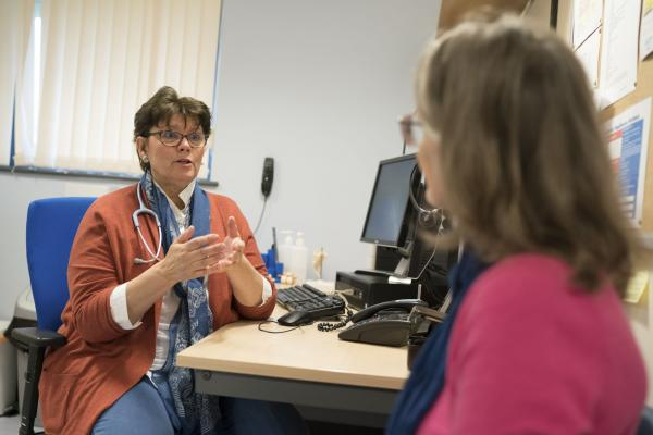 A GP using hand gestures whilst talking to a woman with ovarian cancer