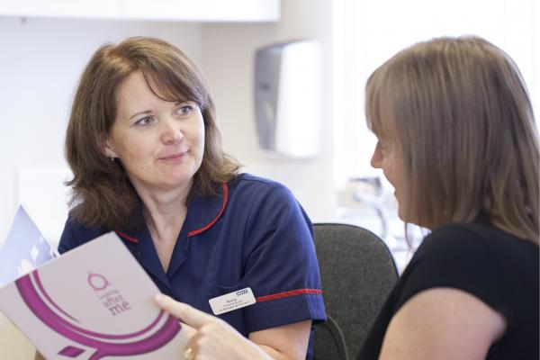 A nurse talking through a Target Ovarian Cancer leaflet with a woman