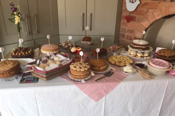 A selection of decorated cakes laid out on a table for afternoon tea