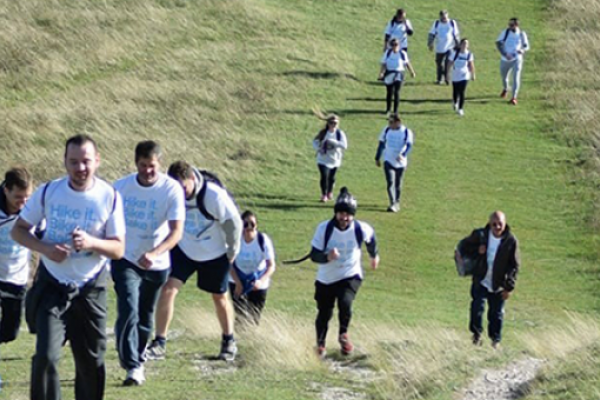 A team of people walking up a steep hill as part of the Chiltern Three Peaks Challenge