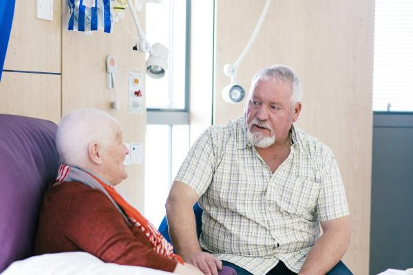 A woman talks to her husband whilst having chemotherapy