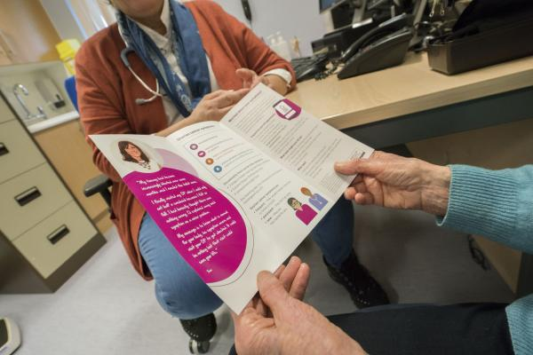 Close up of a woman holding an open Target Ovarian Cancer information leaflet