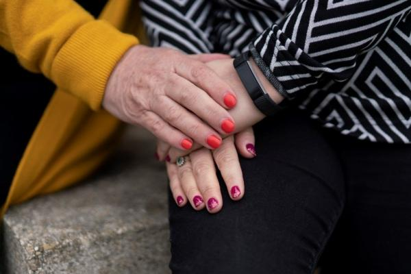 Close up of two people with painted nails holding hands