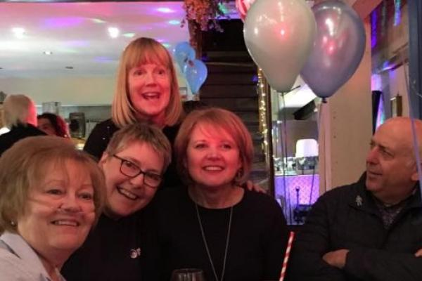 Four women and a man enjoying a birthday party fundraiser