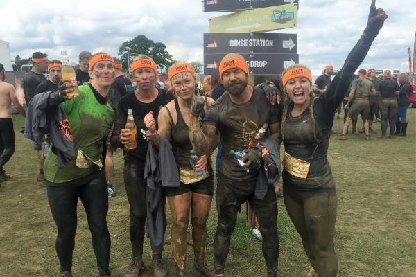 Group photo after finishing a very muddy Tough Mudder challenge