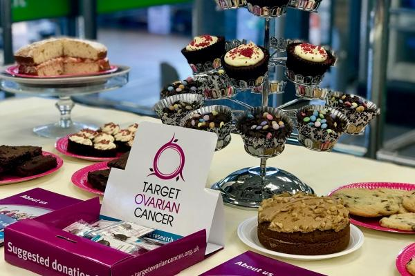 Target Ovarian Cancer bake sale with cupcakes, layer cakes and charity pin badges and leaflets on a table
