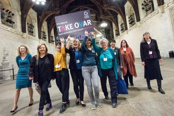 Target Ovarian Cancer campaigners walking through parliament holding a TAKE OVAR placard