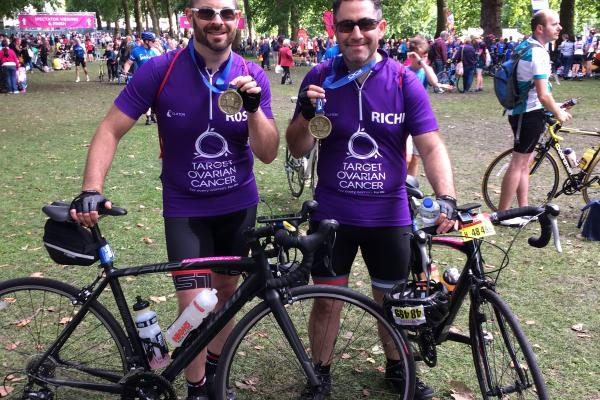 Two Target Ovarian Cancer cyclists at the end of their fundraising event holding their bikes and medals