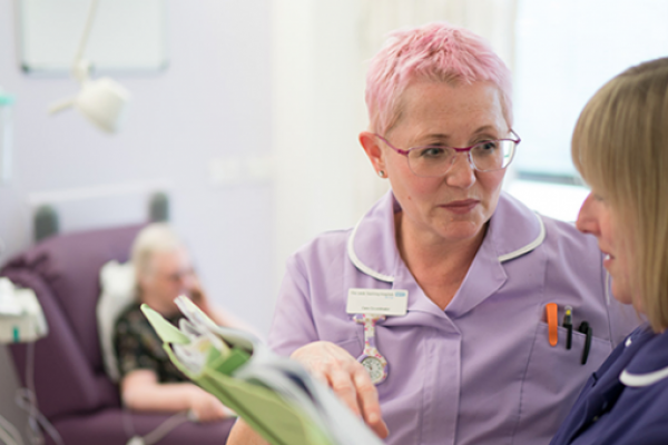 Two nurses discuss patient notes in a chemotherapy unit