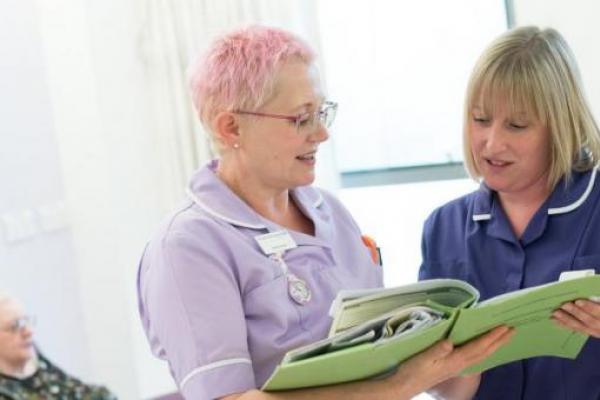 Two nurses discussing patient notes in a chemotherapy unit