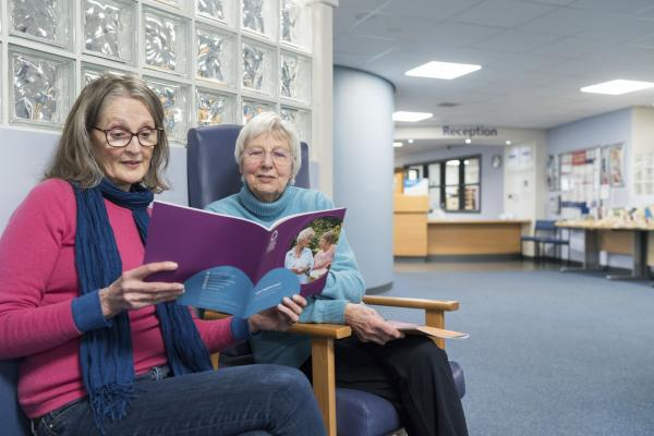 Two women reading a Target Ovarian Cancer guide in a hospital