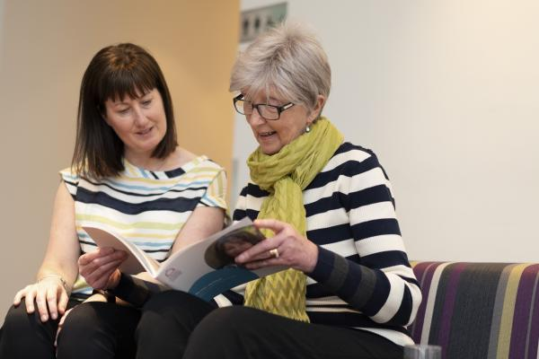 Two women reading a Target Ovarian Cancer guide