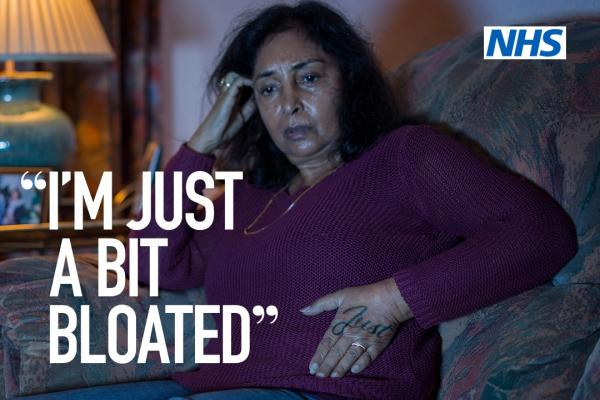NHS campaign poster which reads 'I'm just a bit bloated' on an image of a woman sitting on her sofa looking concerned, with the NHS logo and text reading 'If it last for three weeks or more just speak to your GP – Clear on cancer – help us help you'