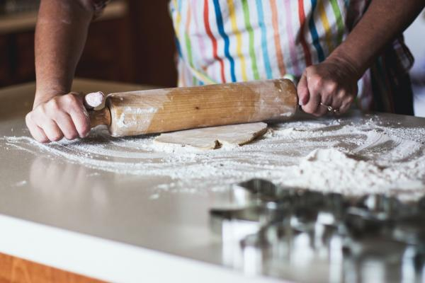 A baker rolling out dough on a floured surface