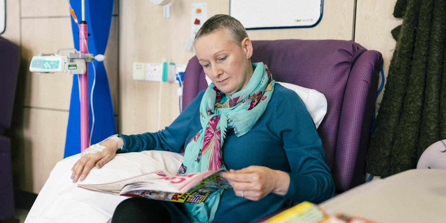 A woman reading a magazine while having chemotherapy