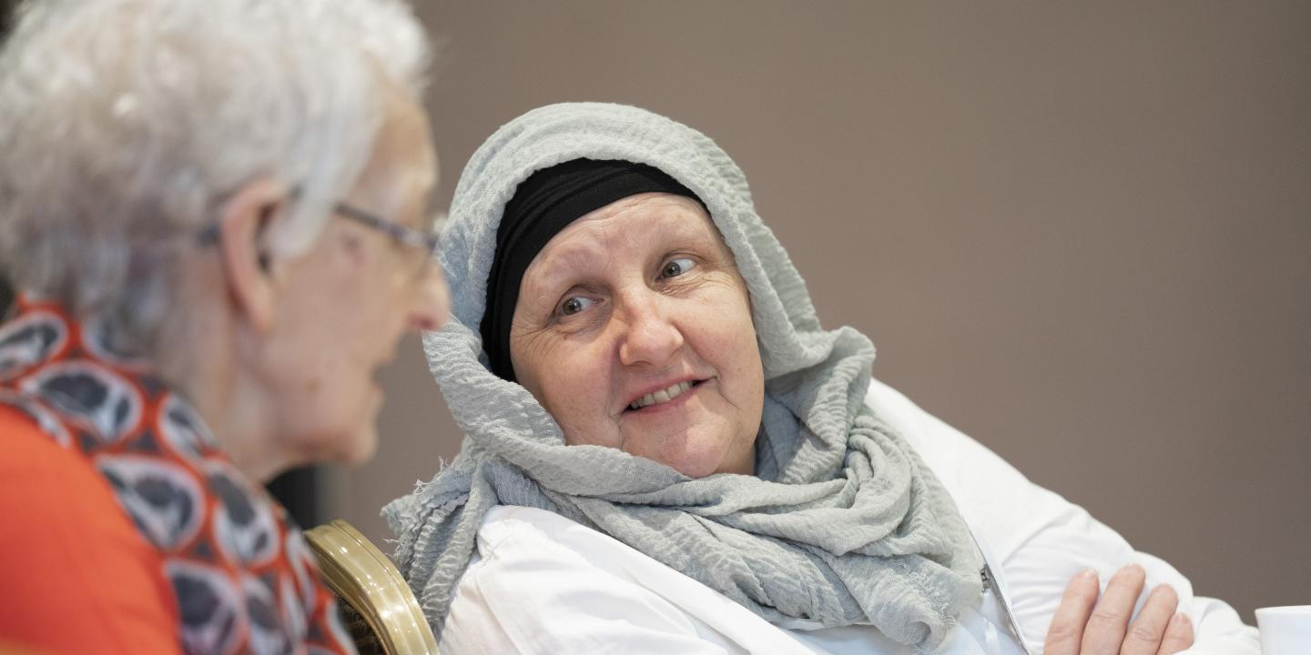A woman with ovarian cancer wearing a head covering talking to another woman