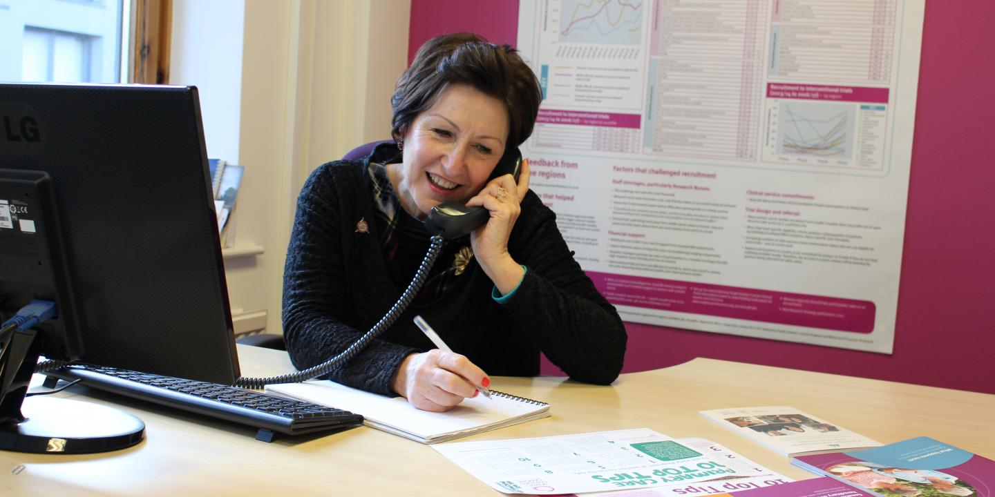 Target Ovarian Cancer Nurse Adviser, Val Lang, smiling while taking a call on our support line