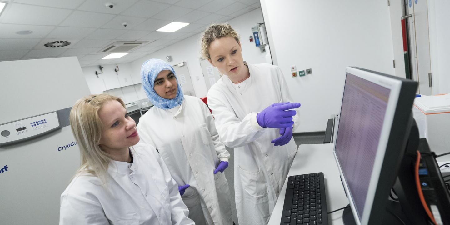 Three female researchers wearing lab coats looking at and pointing to information on a computer screen