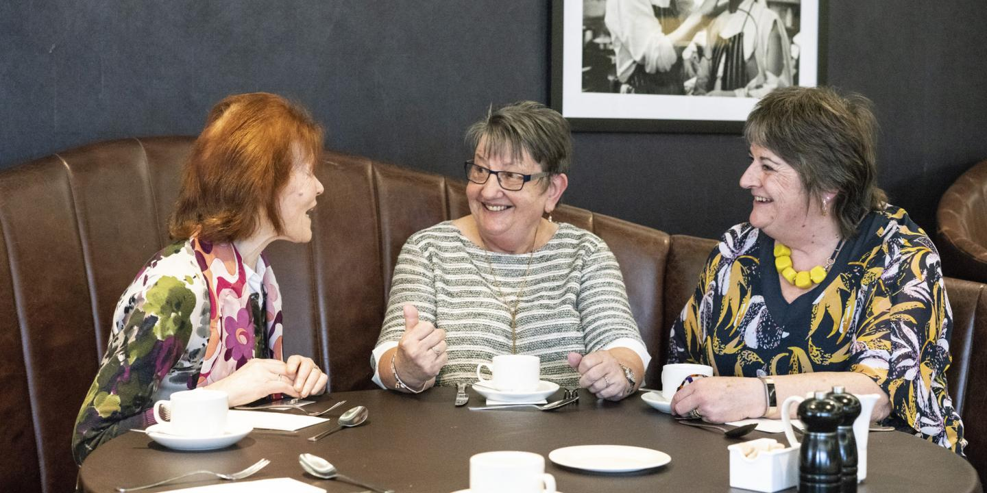Three women talking to and supporting each other