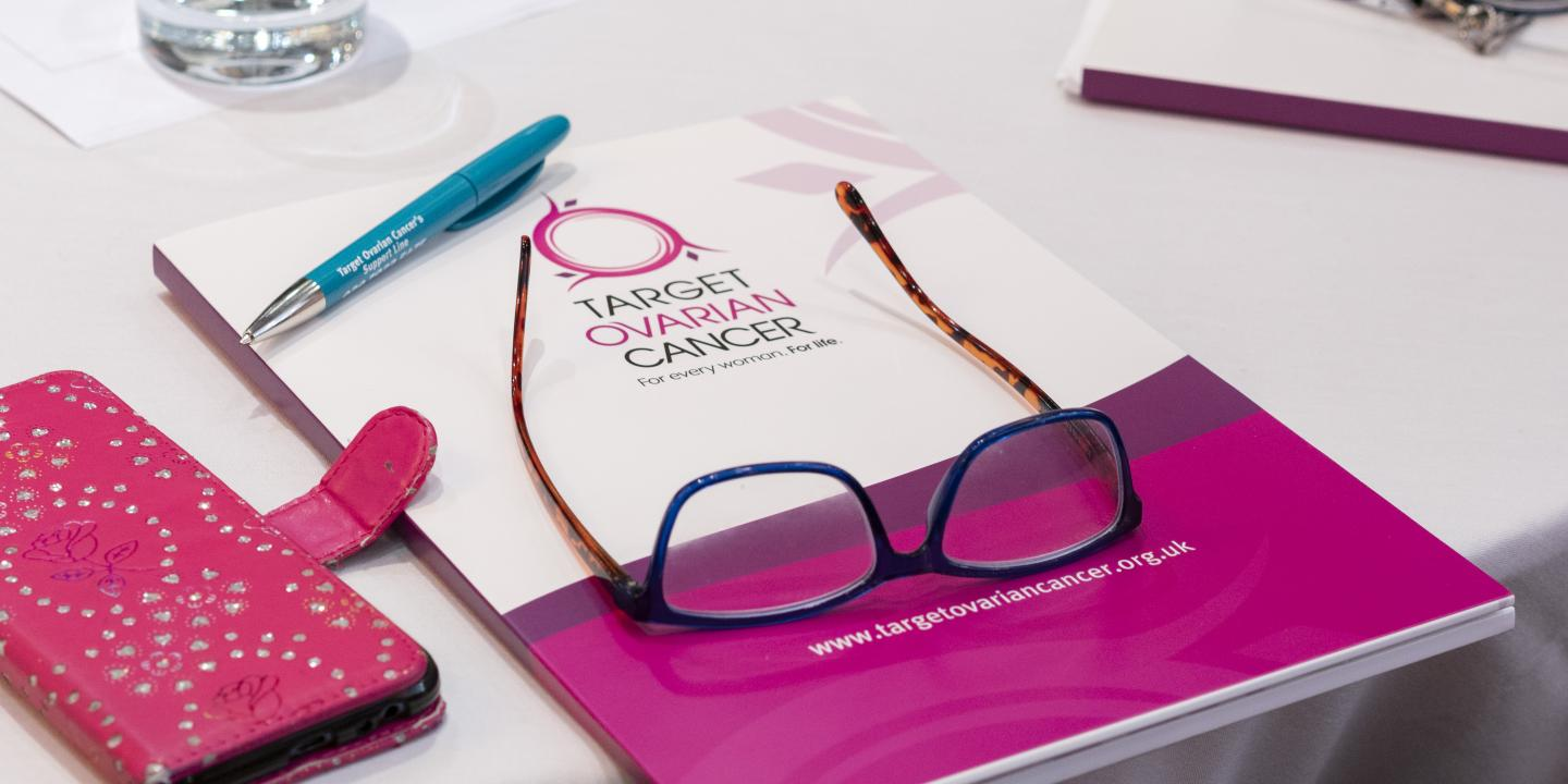 A Target Ovarian Cancer booklet with a pair of glasses on top and a phone next to it in a pink case