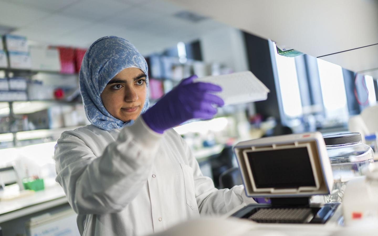A female ovarian cancer researcher wearing a headscarf, purple gloves and a lab coat using equipment