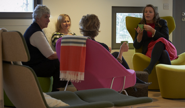 People sitting in comfortable chairs and talking at a cancer support centre