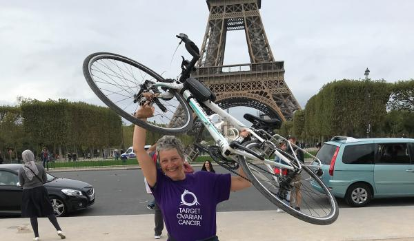 Sara, a Target Ovarian Cancer fundraiser, holding her bike up in the air in front of the Eiffel Tower