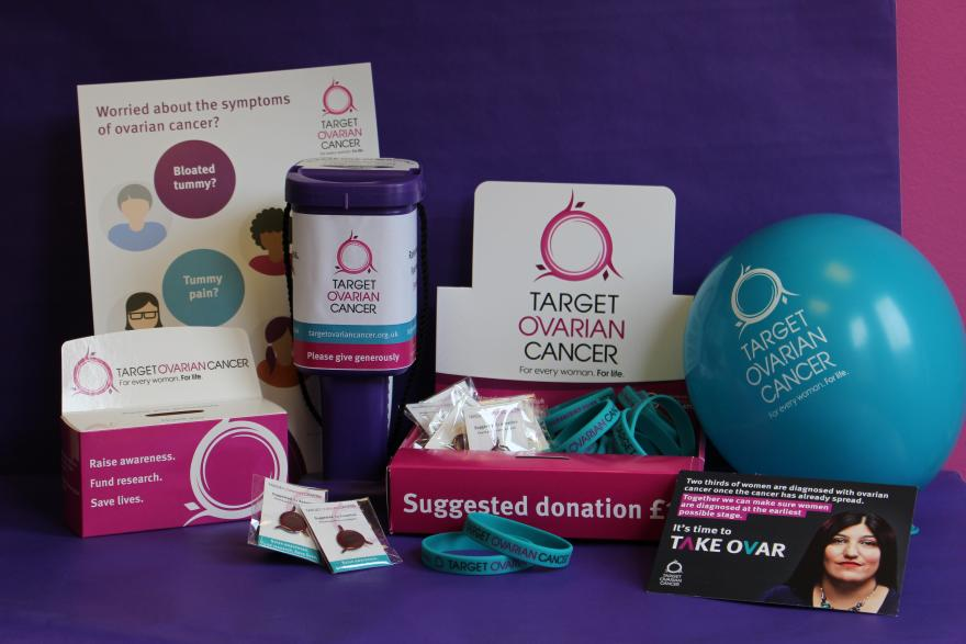 An array of Target Ovarian Cancer fundraising and awareness materials, including a collection box, collection tin, balloon, pin badges, wristbands, leaflets and posters