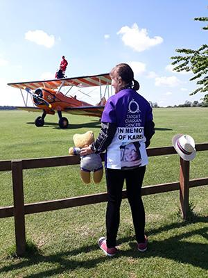 Elaine looking at a biplane holding her daughter's teddy bear