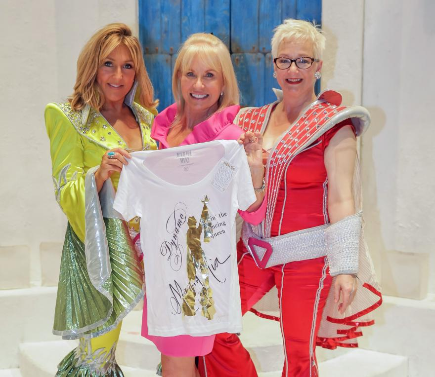 The cast of MAMMA MIA! holding the DYNAMO Target Ovarian Cancer charity t-shirt