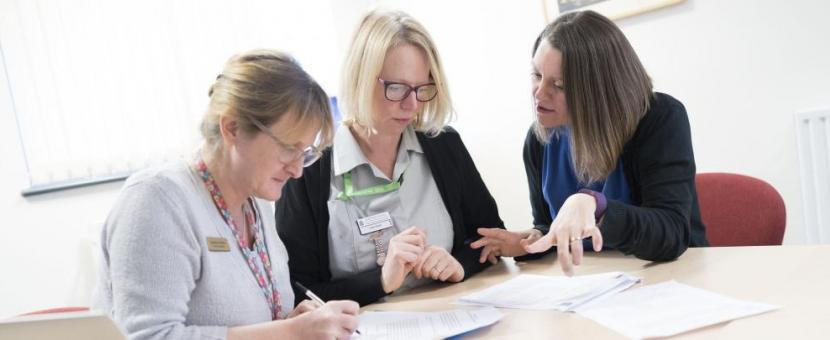 Three female healthcare professionals discuss information at a table