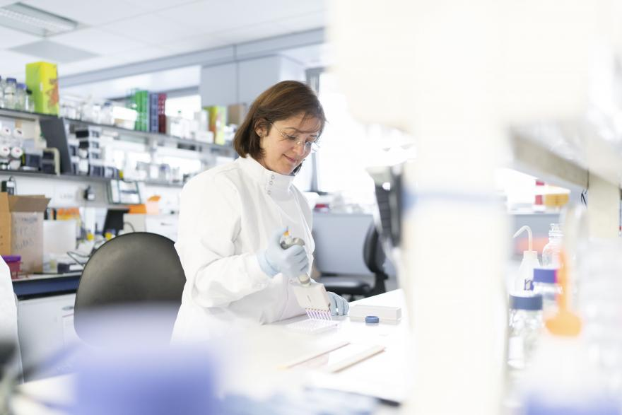 A female ovarian cancer researcher smiling while working in a lab