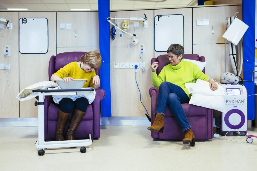 Two women laughing during chemotherapy