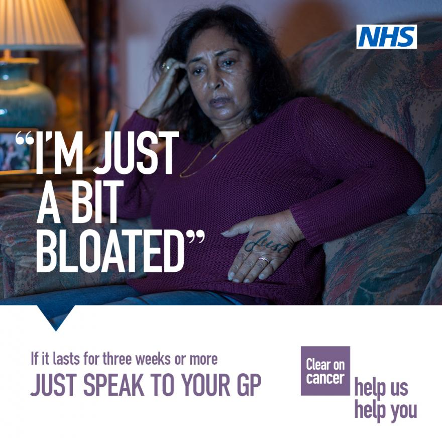 NHS campaign poster which reads 'I'm just a bit bloated' on an image of a woman sitting on her sofa looking concerned