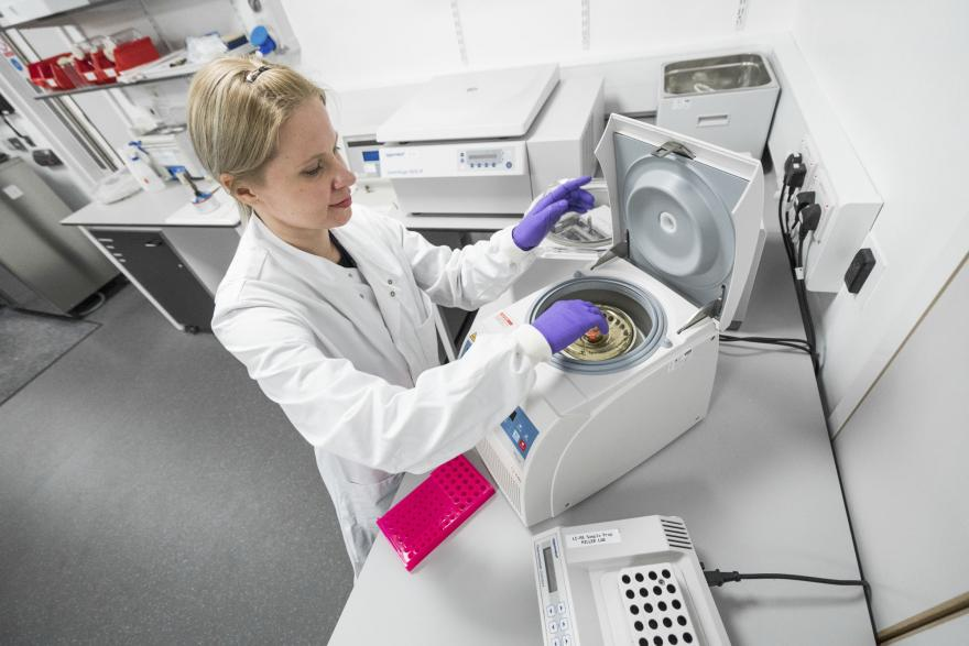 A female ovarian cancer researcher using equipment in a lab